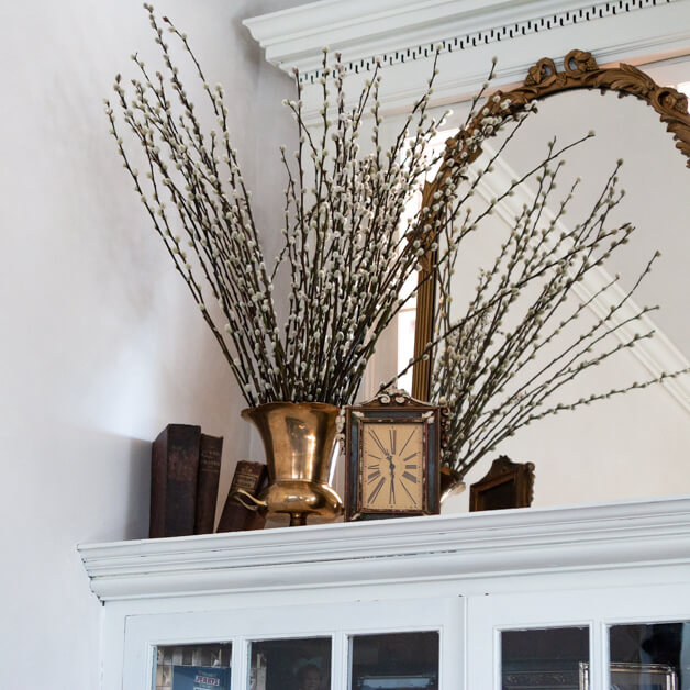 pussy willow in vintage brass vase with vintage clock